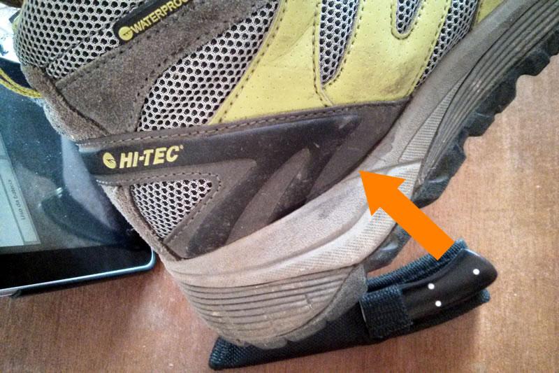 A seta indica o ponto em que a bota descolou, nos dois pés.